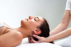Close up of chiropractor pressing back of womans head. Therapist doing healing massage with fingers at back of neck.